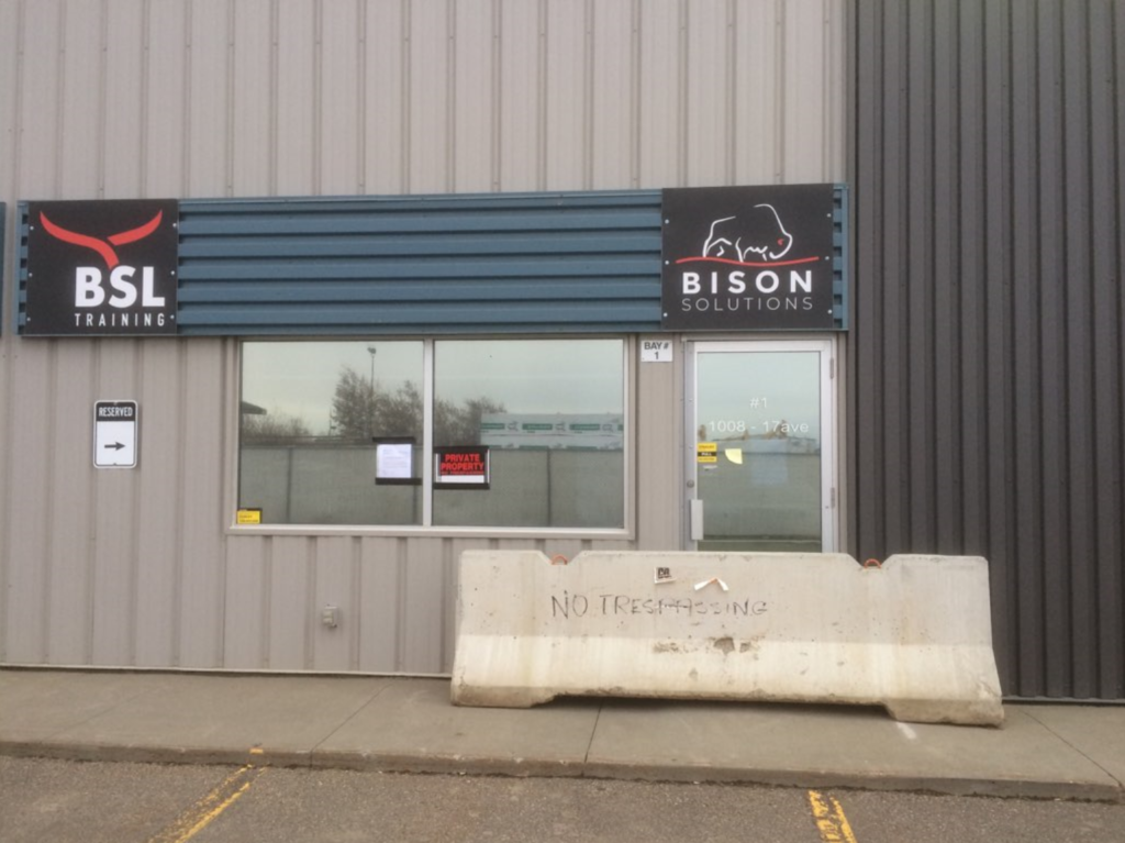 Bison Solutions Ltd. evicted and out of business. Cement blocks blocking off entrance.